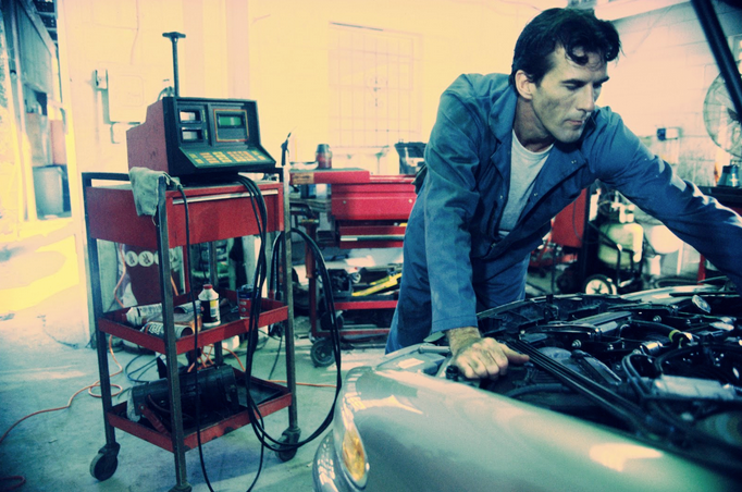 Car maintenance technician checking under hood image